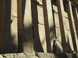 a man praying against a pillar of a rock hewn church in Lalibela